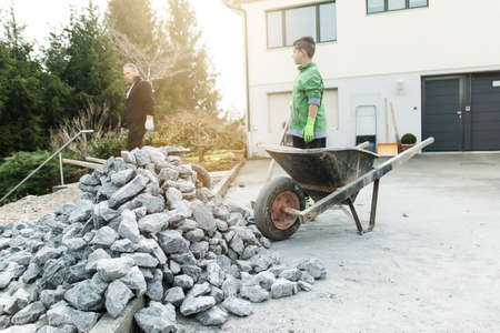 Pile of granite stones in front of wheelbarrow and worker photo