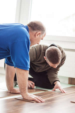 two handymen laying wooden laminate floor together Stockfoto
