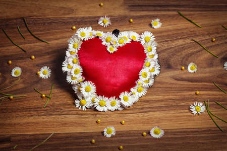 marguerites: greeting card of heart with marguerites and butterflies on wooden board