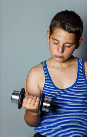 concentrated: Concentrated teenager boy lifting dumb bell