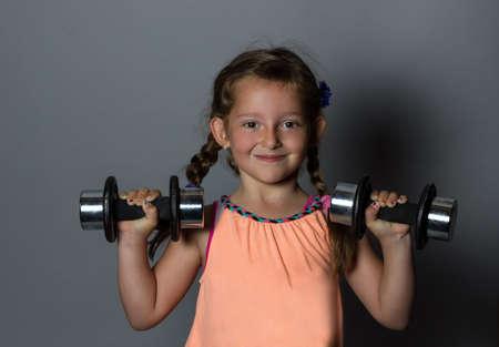 dumb: young smiling girl lifting dumb bell Stock Photo