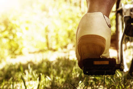 bloomy: shoe on the bike pedal in front of bloomy sunny nature background Stock Photo