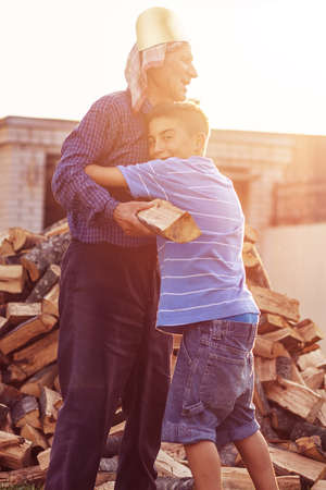nephew: Nephew huge grandfather outside in front of stack of wood Stock Photo