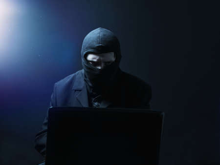 angry computer: Angry computer hacker in suit stealing data from laptop in front of black background and blue light