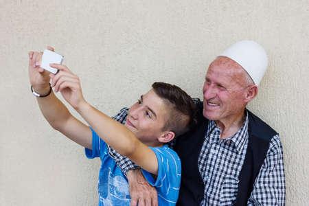 nephew: nephew taking selfie with smiling grandfather