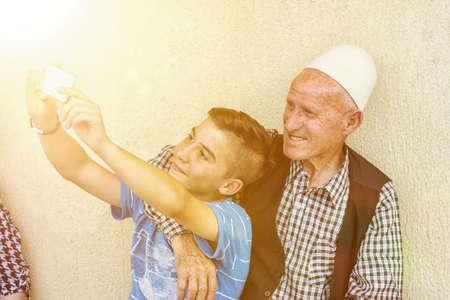 nephew: nephew taking selfie with grandfather in the sunshine