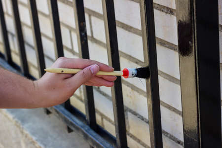 young worker: hand with brush painting metal fence