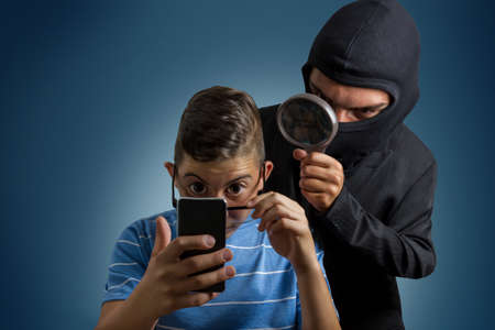 comic masked man spying data from smartphone of teenager