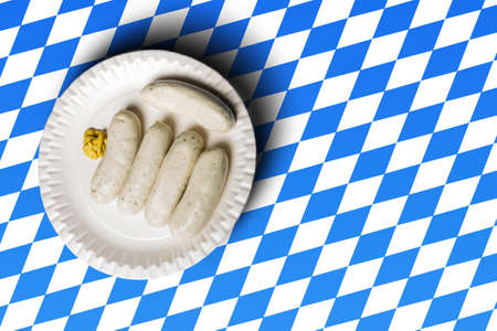 veal sausage: traditional bavarian sausages on white plate and bavarian flag