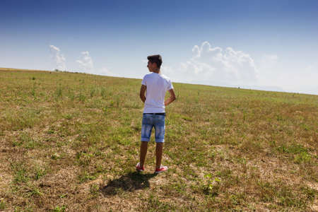 free standing: alone teenager standing on wide free grassland