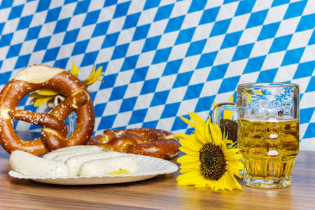 weisswurst: glass full of beer with prezels and traditional Bavarian sausage in front of bavarian flag Stock Photo