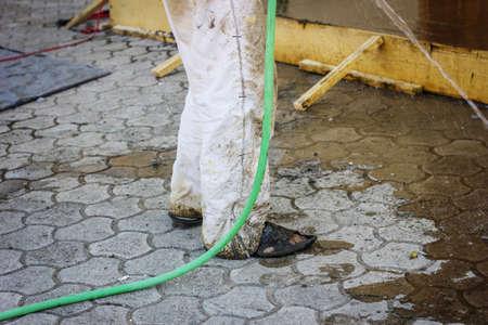 pieds sales: les pieds sales de travailleurs avec des sandales debout avec le tuyau d'eau Banque d'images