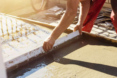 leveling: Leveling wet concrete surface with a metal screed board in evening sunshine