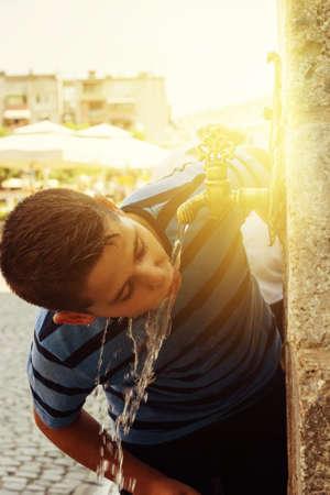 agua grifo: chico beber agua de grifo oriental en la ciudad de Prizren
