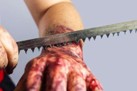herida: el corte en la mano ensangrentada con hoja de sierra delante de fondo gris Foto de archivo