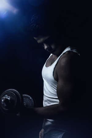 flexing: view of muscular young man flexing biceps with dumbbell in front black background Stock Photo