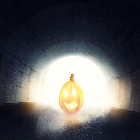 darken: lighten jack-o-lantern in front of darken tunnel with fog and light at the end of tunnel Stock Photo
