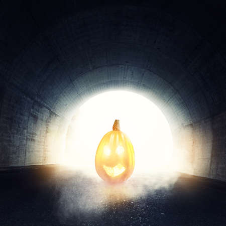 lighten: lighten jack-o-lantern in front of darken tunnel with fog and light at the end of tunnel Stock Photo