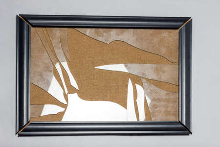black picture frame with broken glass plate in front of grey background Stockfoto