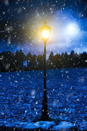 estado del tiempo: lighten street lantern in a field with fallen snow flakes