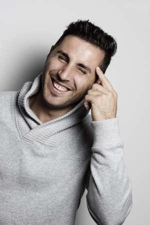 caras felices: Hombre de risa atractiva apuntando con el dedo la cabeza
