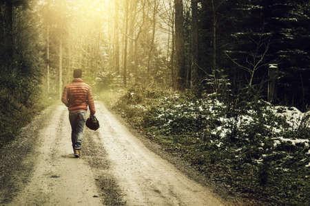 sendero de la naturaleza a través del bosque cubierto de nieve y caminar hombre solo contra la niebla y el sol