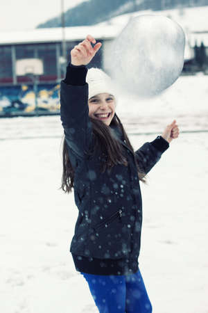 snow ball: young smiling girl throwing snow ball