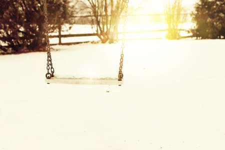 warm things: Empty swing with snow on it in the winter season in front of evening sunshine