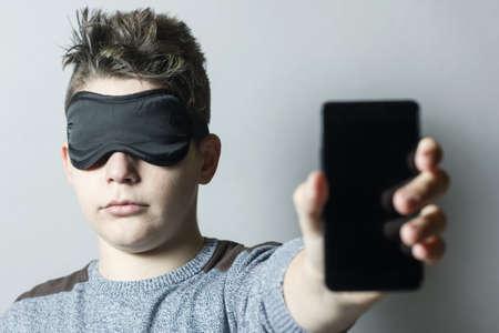 sleep mask: sleepless boy with sleep mask holding and showing smart phone