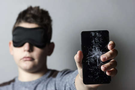 breakage: sad teen with sleep mask is worried because of breakage glass of smart phone in front of grey background