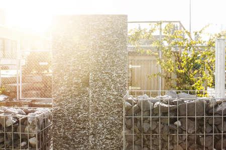 gabion mesh: nature stone granite steles with granite gravel fence. Gabione garden wall in the evening sunshine Stock Photo