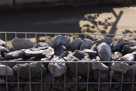 gabion: granite gravel into metal mesh. Gabione garden wall