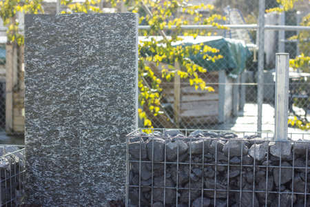 gabion mesh: nature stone granite steles with granite gravel fence. Gabione garden wall Stock Photo