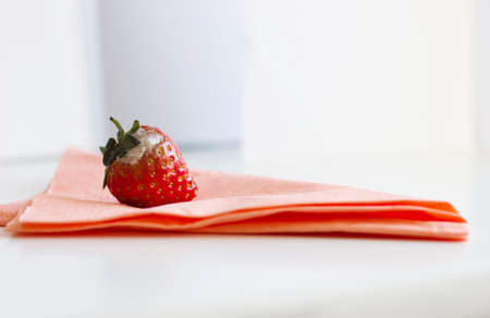 serviette: red strawberry with white mouth laying on pink serviette Stock Photo