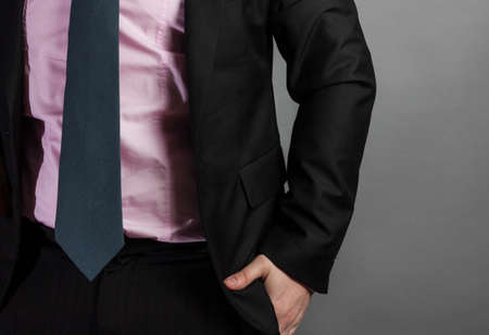 trouser: businessman with tie and suit insert hand in trouser pocket in front of grey background