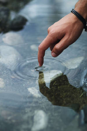 raindrops: finger of one touching the surface of water of a stream Stock Photo