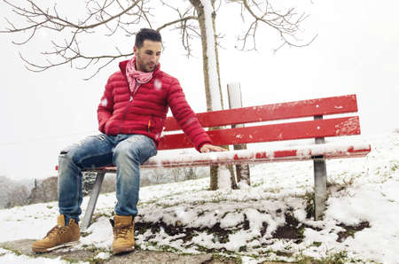 single man sitting on red bench at winter and missing someone Stock Photo