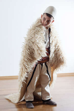 young boy in traditional albanian clothing looking sideways with sheepskin mantle Stock Photo
