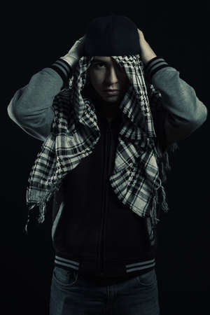 cool boy in hip-hop style set cap over head with scarf Stock Photo