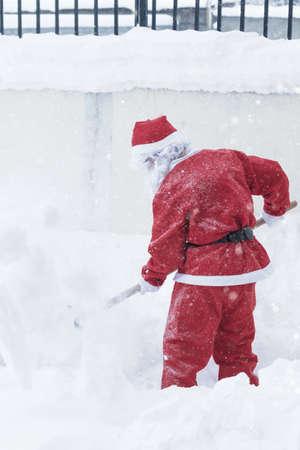 santa claus taking with shovel snow away to make the way free