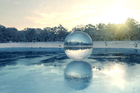 3d rendering of crystal ball on frozen lake in the evening sunlight