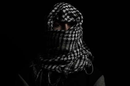 hidden man with palestinian scarf over head in front of isolated black background Standard-Bild