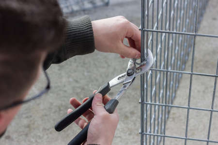 handyman with plier attaching the steel rings at metal fence
