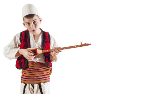 young boy in traditional albanian costume playing traditional string instrument