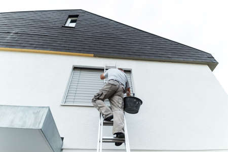 plasterer climbing up the ladder to cover the roof underside with render Stock Photo