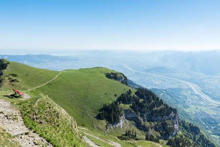 rheintal: Mountain meadow of Hoher Kasten with red bench in front of valley of Rheintal, Canton St. Gallen