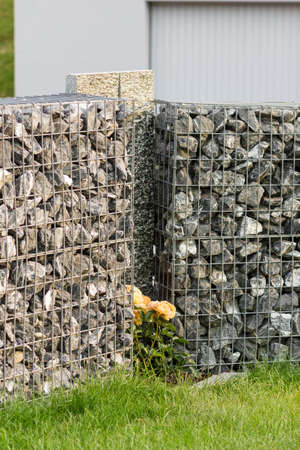 gabion mesh: Grey gabione with gravel stones and stone plates in front green grass