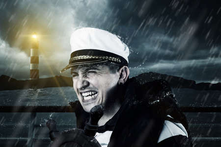 helmsman with vest and cap struggle against storm in front of the coast and light tower