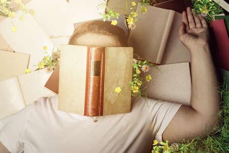 Vista dall'alto di un lettore che dorme e posa su libri ed erba Archivio Fotografico - 89317452