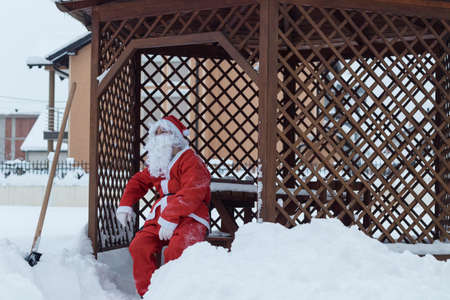 Tired santa claus sitting on wooden chair after work of snow removal in front of wooden house Stock Photo